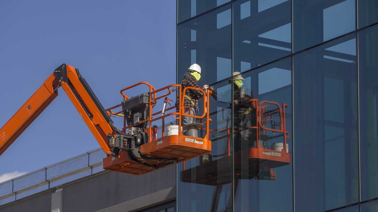 Commercial window replacement contractor working on windows
