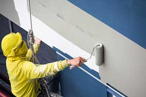 Commercial painter applying exterior paint to building