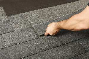 Worker replacing with new roof shingles. Roof replacement offers so many benefits over a roof repair
