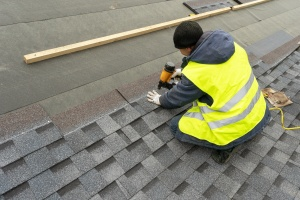 Qualified workman in uniform working as a Roofing Contractor with workmanship warranty