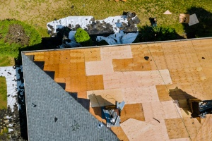 A roofer nailing shingles with air gun to replace roof before selling home
