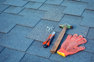Close up view on asphalt shingles on a roof with hammer, nails and stationery knife.