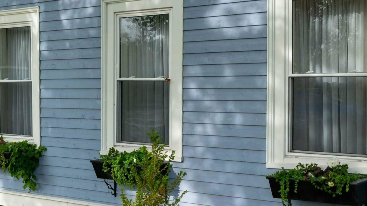exterior wall of a building with three tall double hung windows