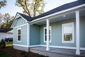front view of a brand new construction house with blue vinyl siding
