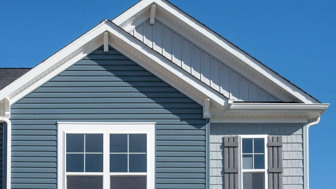 vertical siding in a double gable roof with white decorative corbels