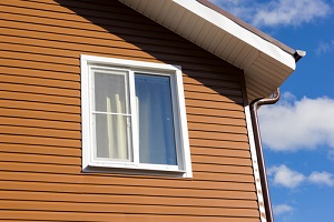 window in the wall of brown vinyl siding