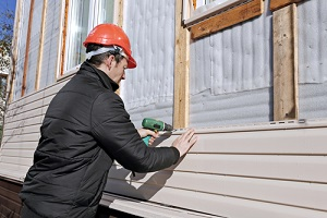 how to tell you need to replace your siding- worker installs panels beige siding on the facade of the house