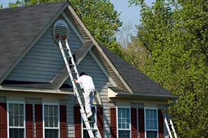 Northern VA siding installation contractor climbing ladder