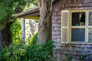 old house with ceder shake siding and a big wood porch