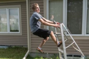 boy falling while working on home siding