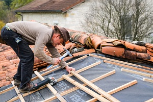 construction worker on a renovation roof covering it with tiles using hammer