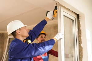workers using electric screwdriver for window installation indoors
