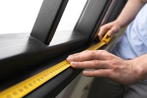measuring wooden window frame indoors