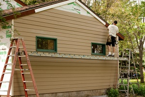 worker installs hardie board siding and flashing to an existing structure
