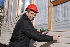 worker replacing home siding