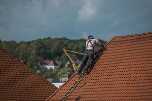 roofing worker using lader to climb the roof