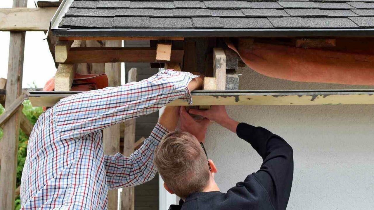 two men father and teen son installing wooden plank frame for eaves of gray asphalt shingles roof