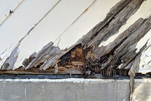 wood siding at an angle with rotting wood and peeling paint atop