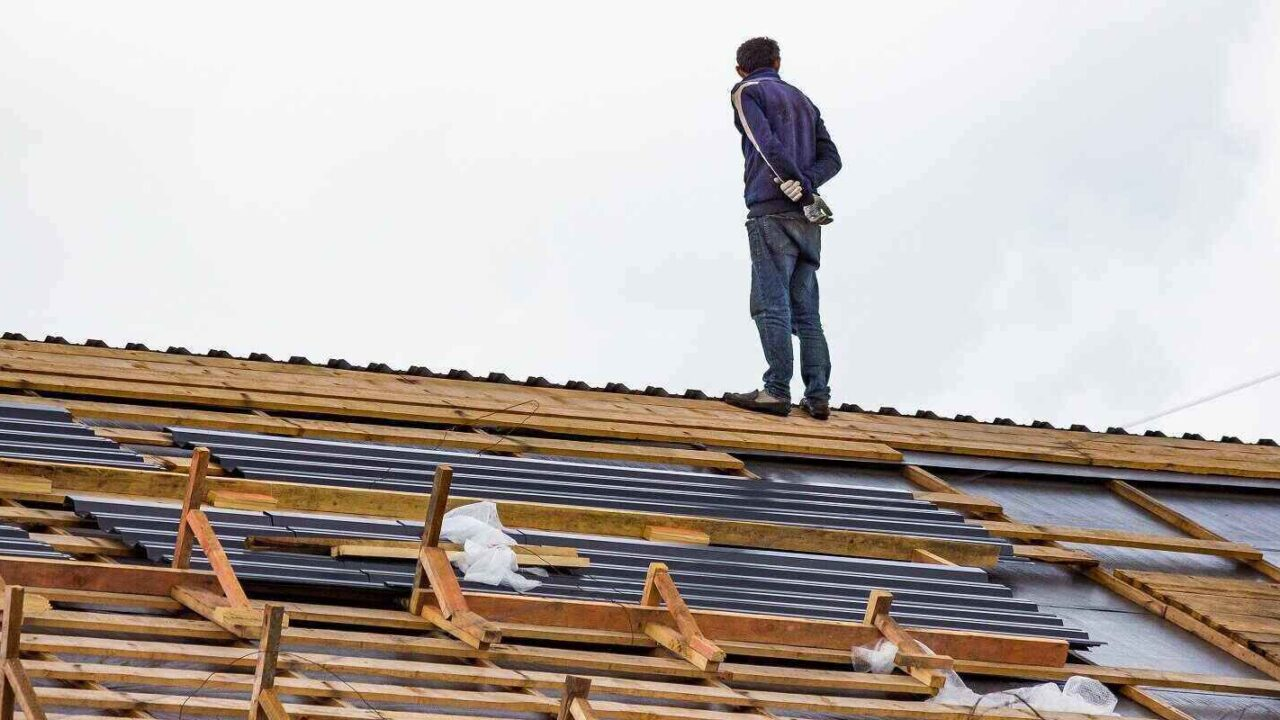 worker stands on roof during roof replacement work